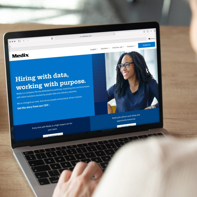 Back view of employee viewing a modern laptop featuring the Medix homepage. Page shows a happy woman, deep blue colors, and Medix's mission statement