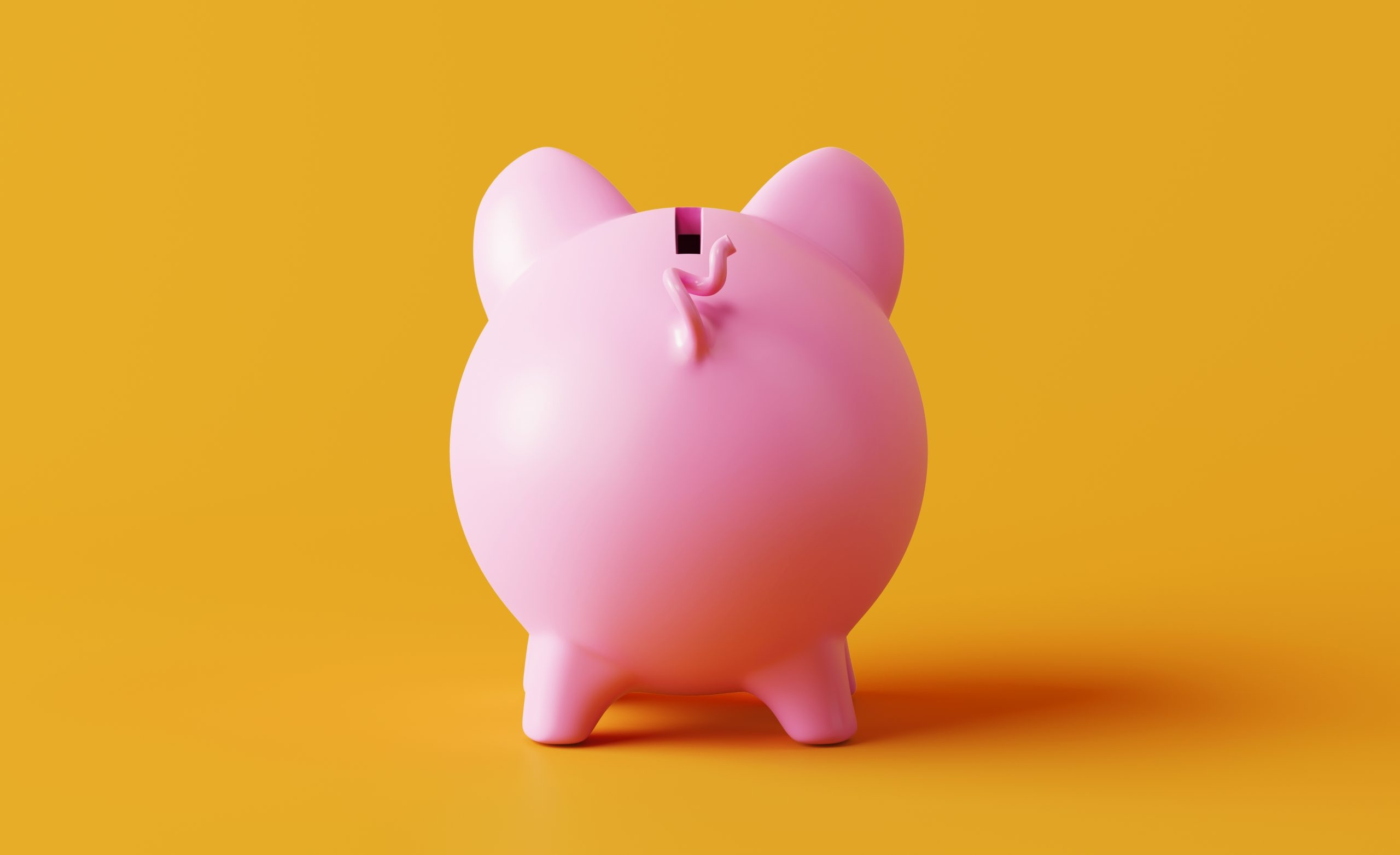 Piggy bank standing on yellow background. Horizontal composition with copy space. Great use for savings concepts.