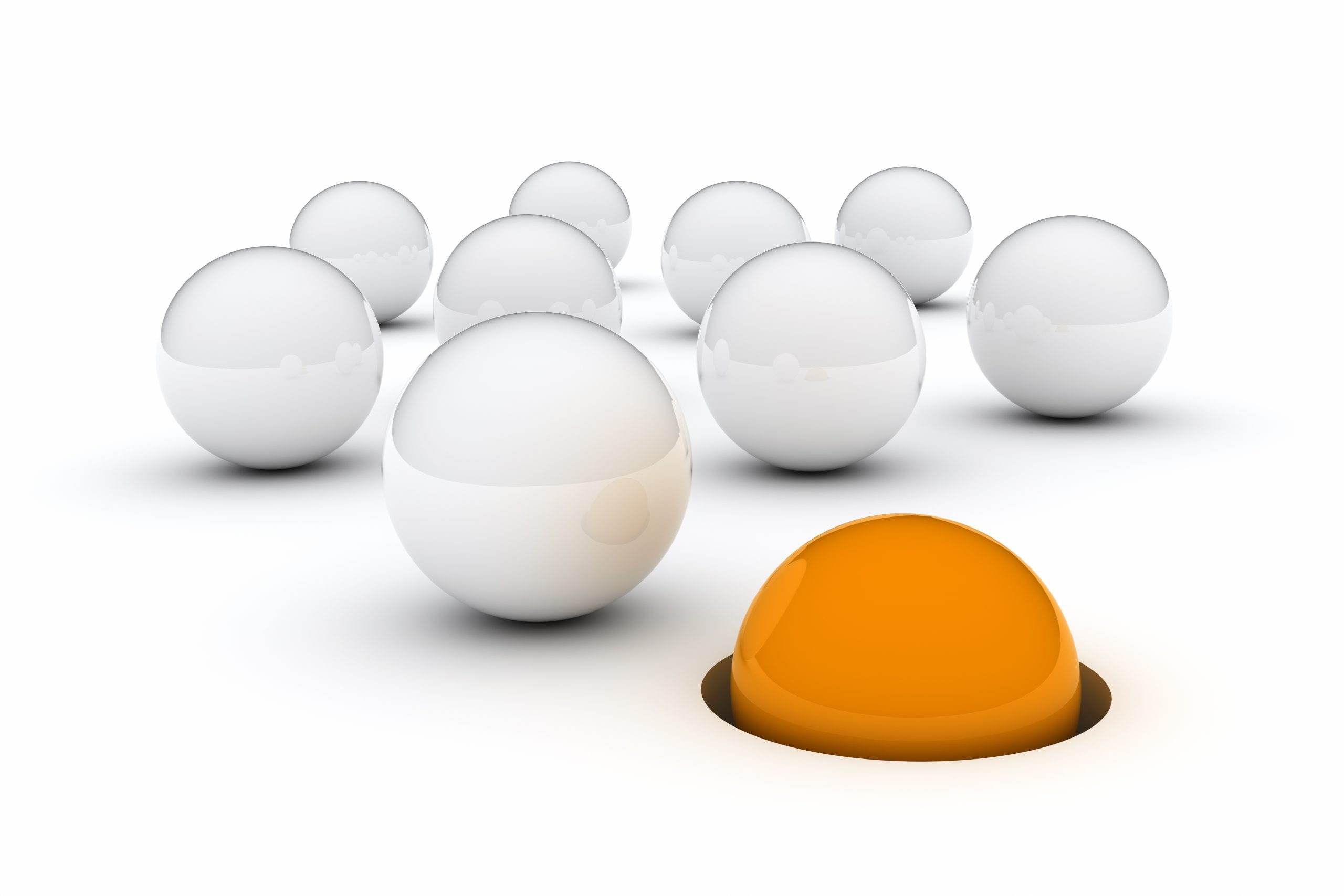 Group of white marbles following an orange marble in a hole in the ground.